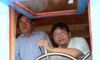 Ông Lê Viết Chữ (bên phải) đang cầm lái chiếc tàu Hoàng Sa ảnh: Văn Chương