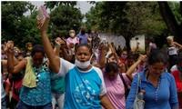 Người thân của các tù nhân ở nhà tù Los Llanos đứng ngoài cầu nguyện cho các nạn nhân vụ thảm sát trong tù.