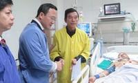 Phó Chủ tịch chuyên trách Uỷ ban ATGT Quốc gia Khuất Việt Hùng động viên bố nạn nhân Ngô Văn Tuấn đang điều trị chấn thương do tai nạn giao thông tại Bệnh viện Việt Đức.