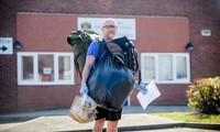 Thầy giáo đi bộ đem thức ăn cho học sinh