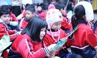 Các em học sinh trường Tiểu học Dịch vọng A dang đọc các thông tin về phân loại rác thải, bảo vệ môi trường