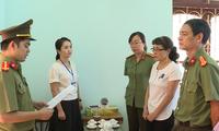 Bị can Nguyễn Thị Hồng Nga (áo trắng bên phải) nghe tống đạt quyết định khởi tố.
