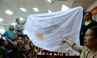 Trước khi buổi tiếp xúc cử tri diễn ra, một số người dân mang theo bản đồ quy hoạch 1/2.000 của khu đô thị mới Thủ Thiêm trưng trước hội trường. Ảnh: Zing