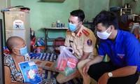 Các chiến sĩ CSGT tặng quà cho người nghèo.