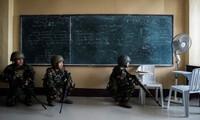 Binh lính Philippines giấu mình trong một lớp học để theo dõi nhóm phiến quân Maute hôm qua, 7/6. Ảnh: AFP