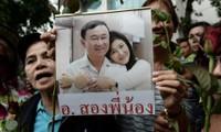 Một người ủng hộ gia đình Shinawatra giơ cao bức ảnh chụp chung của hai anh em cựu Thủ tướng Thái Lan Thaksin và Yingluck Shinawatra. Ảnh: AFP