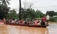 Người dân sơ tán sau sự cố vỡ đập. Ảnh: AFP