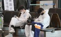 Sinh viên Trung Quốc mặc đồ bảo hộ đang chờ xe đưa đón đặc biệt sau khi đến sân bay Quốc tế Incheon, phía tây Seoul, vào ngày 25/2. Ảnh: Yonhap