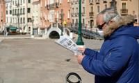 Một người dân đọc báo ở Venice (Ý) ngày 15/3. Ảnh: Reuters