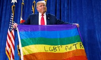 Tổng thống Mỹ Trump cầm lá cờ 7 màu của cộng đồng LGBTQ. Ảnh: Reuters