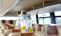 Nhân viên khử trùng xe buýt ở Triều Tiên. Ảnh: Yonhap