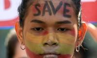 Người biểu tình ở Myanmar viết khẩu hiệu kêu cứu lên mặt. Ảnh: Reuters