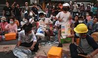 Người biểu tình Myanmar ngồi gõ nắp vung, thùng nhựa trên phố ngày 14/3. Ảnh: Reuters