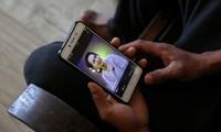 Người Myanmar theo dõi tin tức về cuộc biểu tình trong nước. Ảnh: Reuters