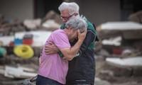 Hai anh em đau buồn khi đứng trước căn nhà bị phá huỷ của cha mẹ ở Altenahr (Đức). Ảnh: CNN