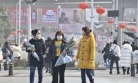 Người đi trên phố ở Vũ Hán đeo khẩu trang để phòng lây nhiễm coronavirus mới. Ảnh: China Daily.