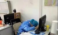 Bác sĩ chống dịch coronavirus mới ngủ gục tại bàn làm việc vì làm việc không nghỉ trong hàng chục giờ. Họ mặc nguyên đồ bảo hộ, đeo bỉm, thậm chí có người cạo trọc đầu... để tiết kiệm thời gian mặc đồ. Ảnh: CCTV News.