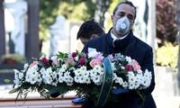 Nhân viên tang lễ và nghĩa trang đeo khẩu trang ở thành phố Bergamo của Italy hôm 16/3. Ảnh: Getty.