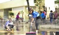 Đoàn viên thanh niên tham gia vệ sinh trường lớp đón học sinh đi lại sau nghỉ bão số 12. Ảnh: Trương Định