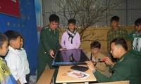 Thượng úy Phạm Tuân (ngoài cùng bên phải) đang lắp đặt chiếc tivi 40 ich mới do anh bỏ tiền túi và kêu gọi bạn bè ủng hộ dành tặng các em học sinh trường THCS Tung Qua Lìn ở huyện Phong Thổ, Lai Châu, tháng 3/2018. Ảnh: Nguyễn Minh