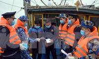 Cán bộ, nhân viên Tàu Cảnh sát biển 2008 và Cục Hải quan thành phố Hải Phòng phát tờ rơi tuyên truyền phòng chống nCoV cho ngư dân