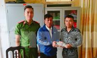 Anh Lương Văn Phú (bìa phải) trả lại 38 triệu đồng đã nhặt được trên đường cho ông Bùi Xuân Hỗ - Ảnh: Hoàng Long