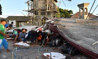 Lực lượng cứu hộ và người dân tìm cách tiếp cận người còn sống và các thi thể dưới đống đổ nát trên đảo Lom bok hôm 5/8. Ảnh: Reuters.