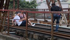 Du khách ngồi trên đường ray cầu Long Biên chụp ảnh