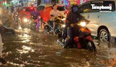 Người dân Sài Gòn lại bì bõm dắt xe lội nước về nhà sau cơn mưa lớn