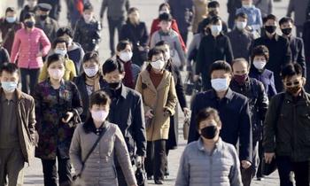 Người dân Triều Tiên đeo khẩu trang khi ra đường. (Ảnh: Reuters)