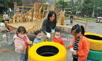 Architect Chu Kim Duc guides the children to participate in the decoration of toys