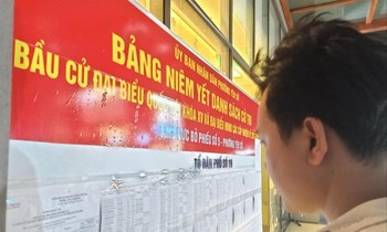 Người dân theo dõi danh sách cử tri được niêm yết tại phường Yên Sở, quận Hoàng Mai, Hà Nội. Ảnh: LD