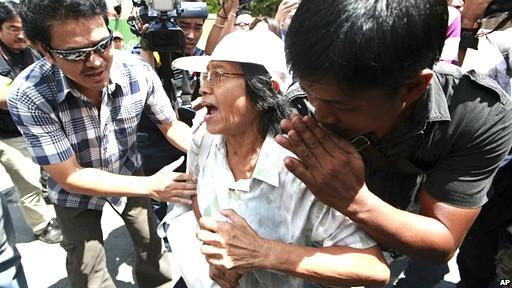 Cảnh sát mặc thường phục tiếp cận trước khi bắt giữ một người biểu tình.