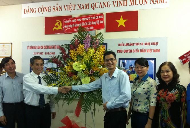 Ông Hứa Ngọc Thuận, Ủy viên Ban Thường vụ Thành ủy, Phó chủ tịch UBND TPHCM tặng hoa cho đại diện báo Tiền Phong.
