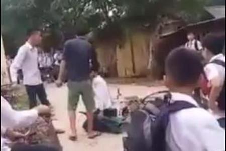 Huy bị đánh và bắt quỳ giữa đường. Ảnh cắt từ clip.