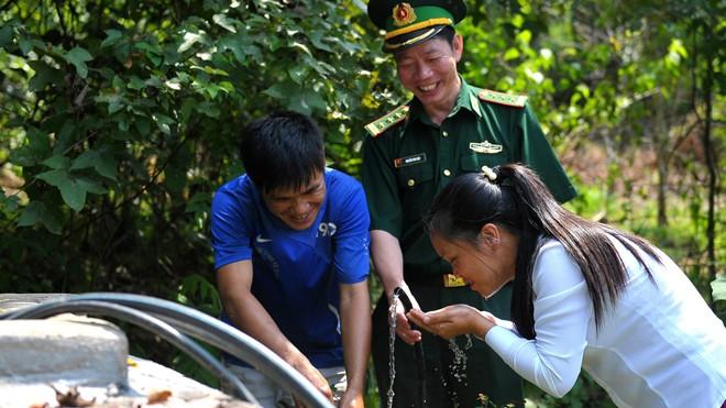 Niềm vui của người lính biên phòng Pò Mã và người dân thôn Nà Lẹng bên bể nước sạch trong thôn. Ảnh: Xuân Tùng.