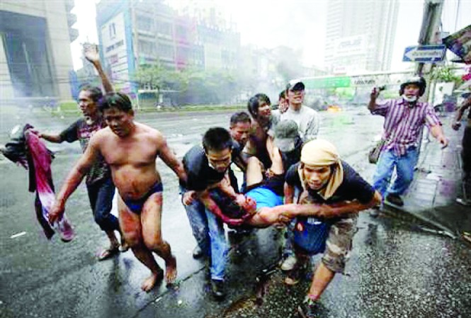 Người biểu tình khiêng một người bị bắn vào đầu