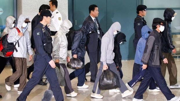 Người đào tẩu Triều Tiên (đeo khẩu trang) tới Hàn Quốc. Ảnh: EPA.