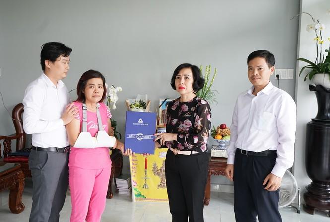 Đại diện Ban giám hiệu trường ĐH Hoa Sen trao bang tốt nghiệp cho bà Liên (áo hồng) mẹ của nam sinh Hải Nguyên