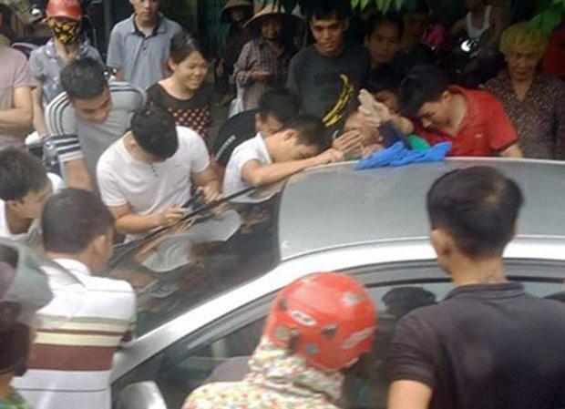 Mọi người cố gắng phá cửa xe giải cứu bé trai bị bố bỏ quên.