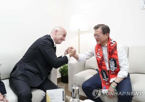 Chủ tịch FIFA Gianni Infantino vật tay với Tổng thống Hàn Quốc Moon Jae-in tại Nga sau khi xem một trận đấu giữ đội Hàn Quốc và Mexico tại World Cup 2018. (Ảnh: Yonhap)