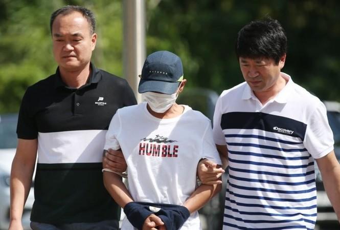 Người đàn ông Hàn Quốc bị tình nghi bạo hành người vợ Việt Nam bị cảnh sát dẫn đi. (Ảnh: Yonhap)
