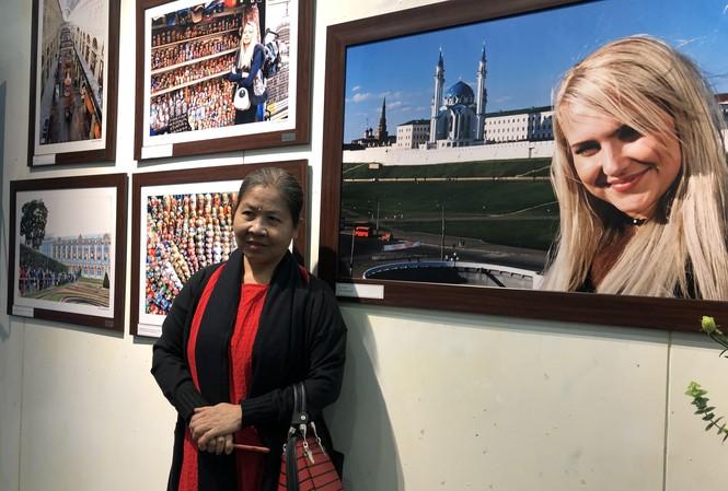 Một người xem triển lãm chụp ảnh lưu niệm bên bức ảnh cô gái Nga. (Ảnh: Thu Loan
