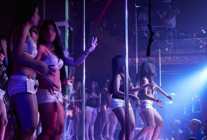 Các cô gái trẻ đang nhảy trên sàn một quán bar ở quận đèn đỏ ở TP Angeles. (Ảnh: SCMP)