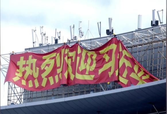 Các công nhân đang treo biểu ngữ chào mừng Chủ tịch Trung Quốc Tập Cận Bình. (Ảnh: Reuters)