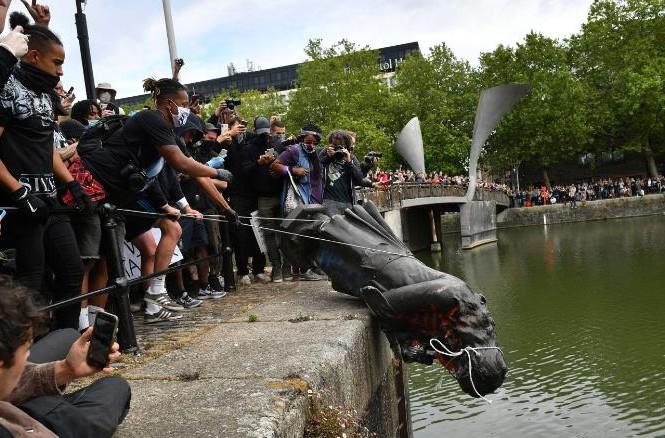 Người biểu tình ở London vứt tượng Edward Colston xuống sông. (Ảnh: CNN)
