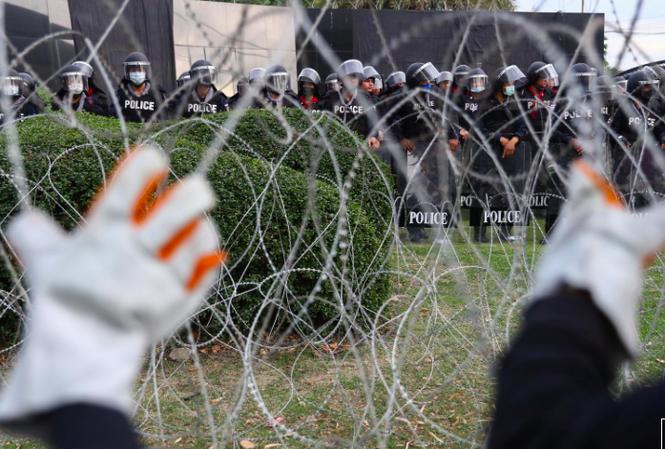 Người biểu tình cố kéo đổ hàng rào dây thép gai khi biểu tình trước Trung đoàn bộ binh số 11. (Ảnh: Reuters)
