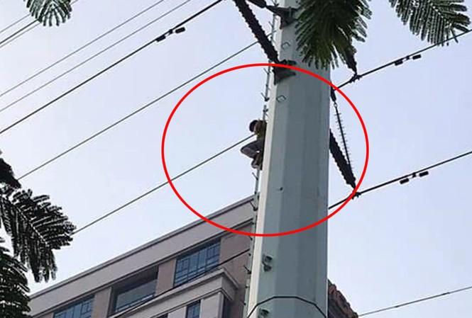 Hình ảnh nam thanh niên ngồi vắt vẻo trên cột điện cao thế.