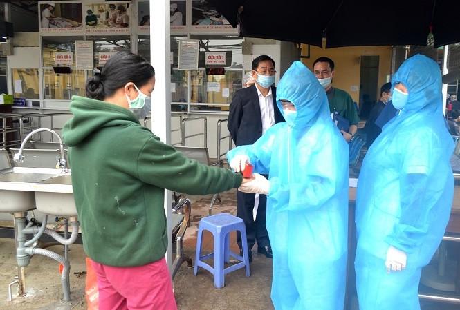 Người dân vào Bệnh viện đa khoa Sơn Tây sẽ phải đo thân nhiệt, khai báo y tế và đóng dấu xác nhận đã được kiểm soát. Ảnh: Đức Vân - Vũ Tuyết