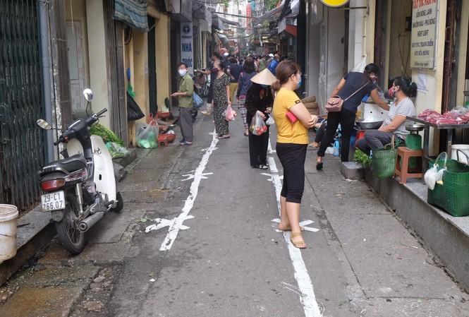 Kẻ sơn, đo thân nhiệt từng người vào chợ Yên Thái (quận Hoàn Kiếm)
